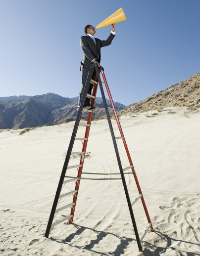 Full length of a mature businessman standing on ladder and yelling through megaphone in desert